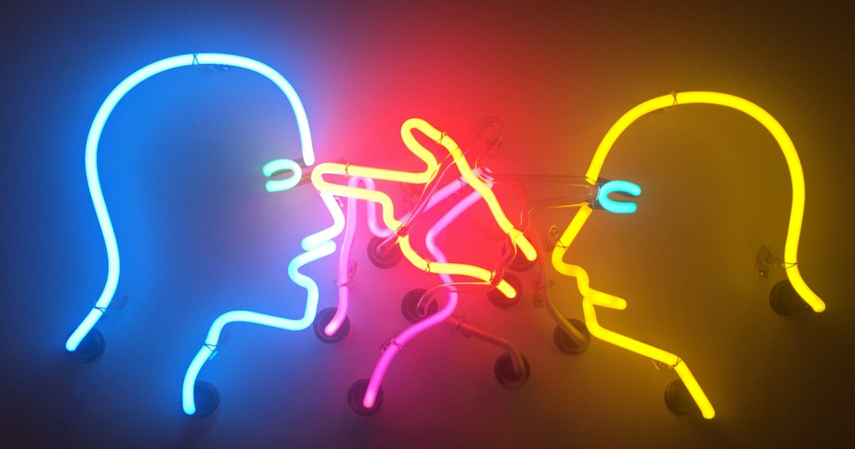 The outline of two heads lit up in neon constantly point at each other in anger. The picture is used to symbolise how a student feels when the examiner interrupts them in the IELTS exam by an examiner