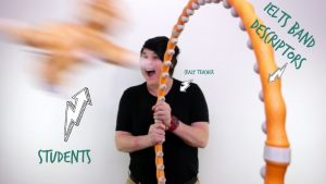 A woman stands holding a hoop with a toy cat jumping through to illustrate the IELTS band descriptors