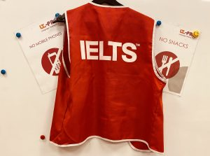 A photograph of the test administrators' bib at an IELTS IDP test centre